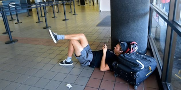 Traveller Santiago Aldrete, who arrived from Bali and is awaiting his flight to Mexico City, gets comfortable on the ground while charging his phone at Los Angeles International Airport on July 1, 2016 where a record 1.207 million people are expected to pass through during their travels over the Fourth of July weekend.    LAX officials said the number of travelers anticipated to use the airport is up 9.7 percent from last year's record 1.1 million people over the holiday travel period, which runs from today through Tuesday July 5. / AFP / Frederic J. BROWN        (Photo credit should read FREDERIC J. BROWN/AFP/Getty Images)