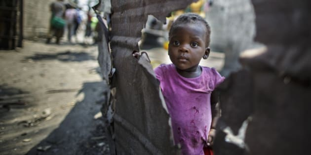 Beira, Mozambique - September 28: A little girl stands behind a broken wall in a slum in the urban area of Beira on September 28, 2015 in Beira, Mozambique. (Photo by Thomas Trutschel/Photothek via Getty Images)