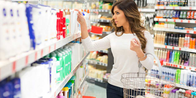 Beautiful young woman searching for perfect beauty product in store