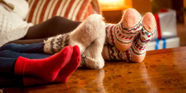Closeup conceptual photo of family warming feet at fireplace