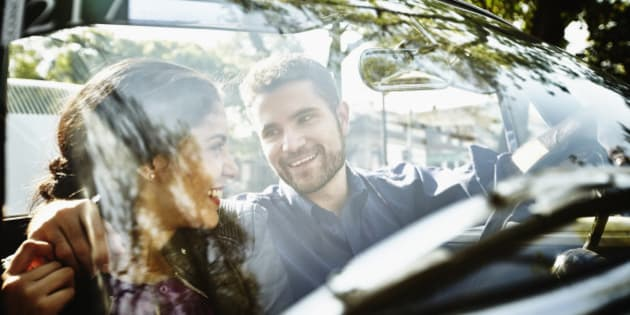 Smiling couple embracing in front seat of convertible