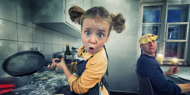 Little girl cooking pancakes or omelettes. One just flew straight on the head of her daddy.