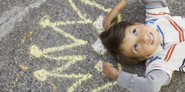 Curious boy with sidewalk chalk crown overhead