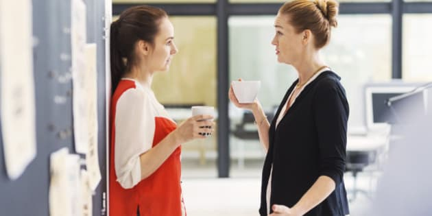Side view of businesswomen discussing while having coffee in office