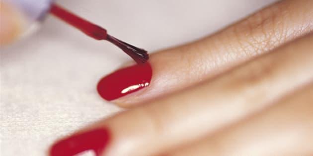 Close-up studio shot of woman applying nail polish