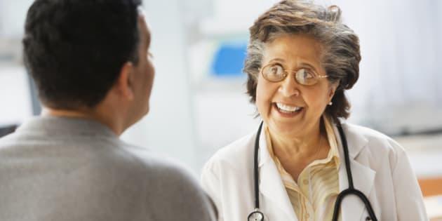 Senior Hispanic female doctor talking to patient