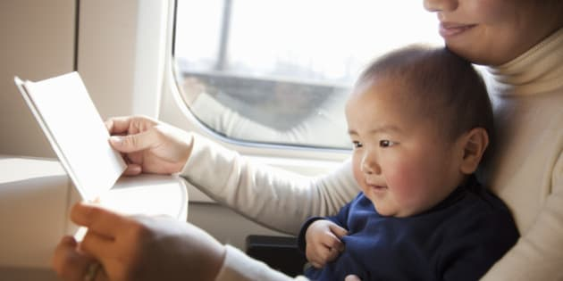 Asian mother is reading a book to her baby on train.