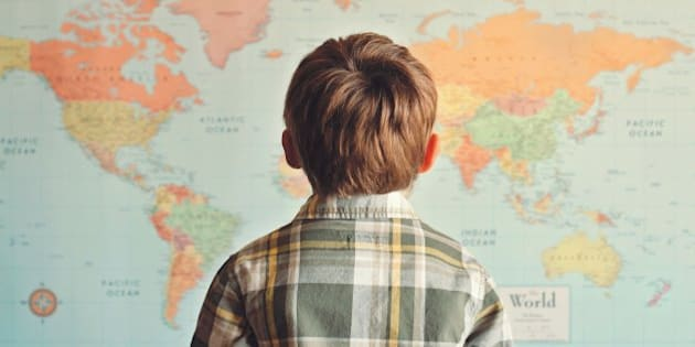 Little boy looking at world map