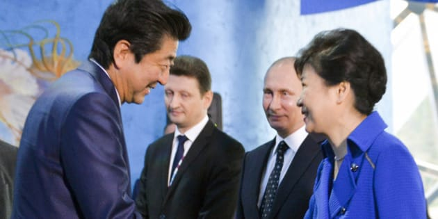 South Korean President Park Geun-hye, right, and Japanese Prime Minister Shinzo Abe, left, shake hands as Russian President Vladimir Putin, second right, watches while visiting an oceanarium on Russky Island where the Eastern Economic Forum takes place in Russian Far Eastern port of Vladivostok, Russia, Saturday, Sept. 3, 2016. (Alexei Druzhinin, Sputnik, Kremlin Pool Photo via AP)