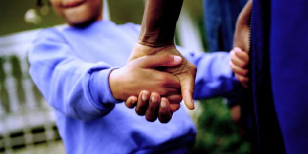 Girl (10-11) holding fathers hands outdoors