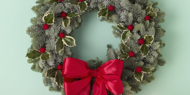 holiday wreath over mantel on green wall