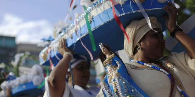 Followers of the Afro-Brazilian religion Umbanda carry offerings and an image of Iemanja, goddess of the sea, in Copacabana Beach in Rio de Janeiro December 29, 2014.Worshippers present gifts to the sea goddess at the end of every year, to give thanks and ask for blessings for the upcoming new year.    REUTERS/Ricardo Moraes(BRAZIL - Tags: SOCIETY RELIGION)