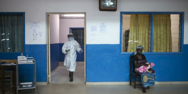 A health worker walks past a woman holding a baby at the maternity ward in the government hospital in Koidu, Kono district, in eastern Sierra Leone, December 20, 2014. Health workers at the hospital are in full protective gear as part of increased precautions since the outbreak of Ebola in West Africa. Sierra Leone, neighbouring Guinea and Liberia are at the heart of the world's worst recorded outbreak of Ebola. Rates of infection are rising fastest in Sierra Leone, which now accounts for more than half of the 18,603 confirmed cases of the virus.  REUTERS/Baz Ratner (SIERRA LEONE - Tags: HEALTH DISASTER)