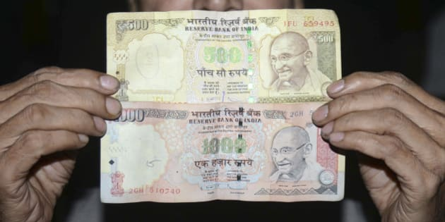 An Indian man holds 500 and 1000 INR notes in Amritsar on November 8, 2016. 