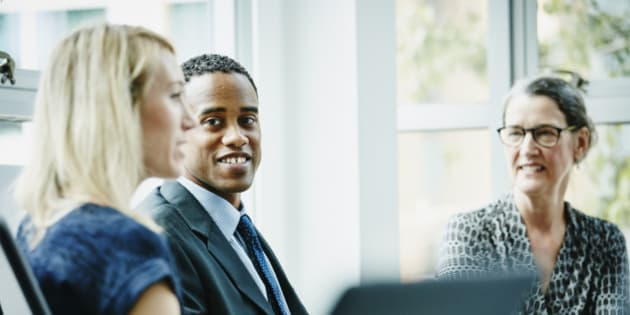 Smiling businessman listening to businesswoman lead discussion during meeting