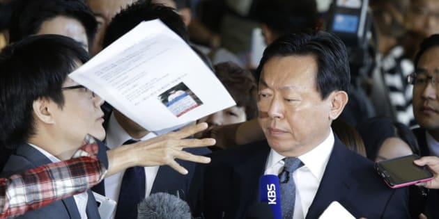 In this Tuesday, Sept. 20, 2016 photo, a bunch of papers is hurled by an unidentified man toward Lotte Group's Chairman Shin Dong-bin, center, as he arrives at the Seoul Central District Prosecutors' Office for the questioning over suspected embezzlement, in Seoul, South Korea. South Korean prosecutors questioned Shin on Tuesday in a corruption probe at the country's fifth-largest business group. (AP Photo/Ahn Young-joon, File)