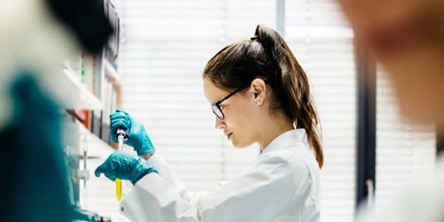 Female scientist using pipette in a modern laboratory, Her female colleague using microscope in foreground