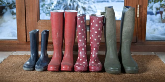 Row of wellies on mat with snow covered garden through windows behind.