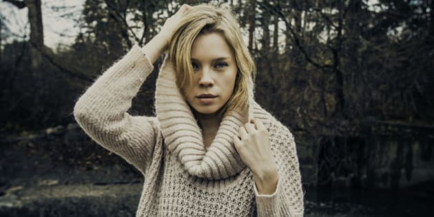 Beautiful blonde model with a large, ribbed-neck sweater by the river.