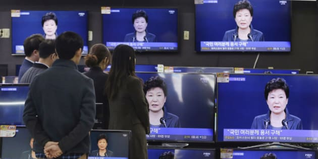 "In this Friday, Nov. 4, 2016 photo, people watch TV screens showing the live broadcast of South Korean President Park Geun-hye's addressing to the nation at the Yongsan Electronic store in Seoul, South Korea. Park took sole blame Friday for a ""heartbreaking"" scandal that threatens her government and vowed she will accept a direct investigation into her actions amid rising suspicion that she allowed a mysterious confidante to manipulate power from the shadows. (AP Photo/Ahn Young-joon, File)"