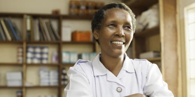 A nurse of East African descent stands proudly in a hospital with medical supplies in the background.