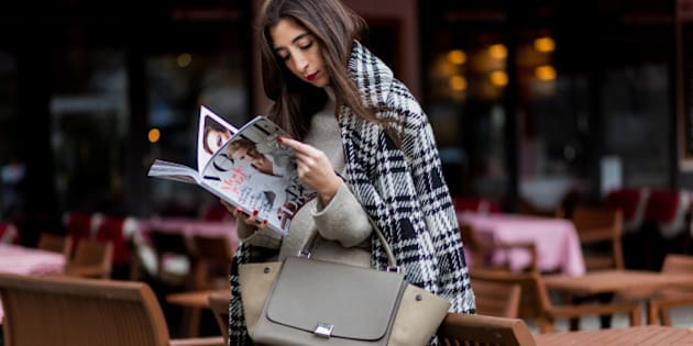 BERLIN, GERMANY - NOVEMBER 7: Nadja Ali (@n_jayjay, the-attitude.com) reading a German Vogue magazine in a French cafe wearing a white black checked Zara coat, a creme Zara jumper, black Zara leather pants, Celine bag on November 7, 2016 in Berlin, Germany. (Photo by Christian Vierig/Getty Images)