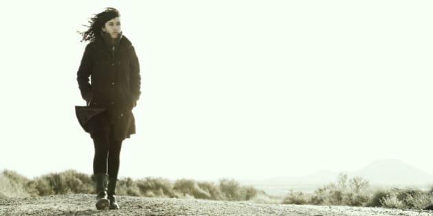 Young woman walking alone in Spain desert called Bardenas Reales, Navarra, Spain