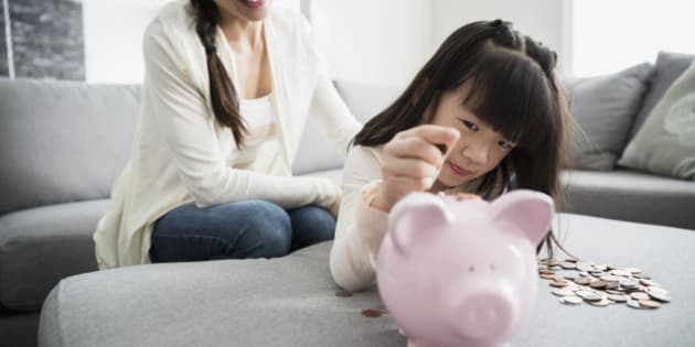 Mother watching daughter deposit coin into piggy bank