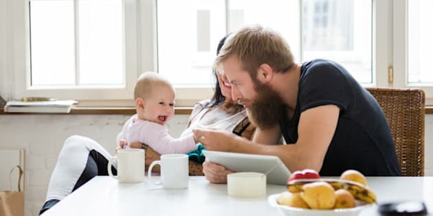 Young mother and father with newborn baby sitting in their kitchen and having fun together