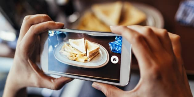 Close up of a young woman taking a photo of a sandwich