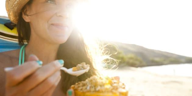 A beautiful woman with a straw hat eating a papaya with fresh granola and yogurt.