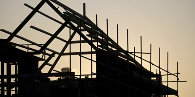 View of a silhouetted timber house in construction