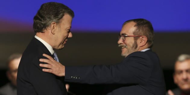 Colombia's President Juan Manuel Santos, left, shakes hands with with Rodrigo Londono, known as Timochenko, top leader of the Revolutionary Armed Forces of Colombia, FARC, after signing a revised peace pact at Colon Theater in Bogota, Colombia, Thursday, Nov. 24, 2016. An original accord ending the half century conflict was rejected by voters in a referendum last month. (AP Photo/Fernando Vergara)