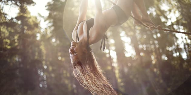 Young girl hanging upside down from a rope with the sun flaring behind her