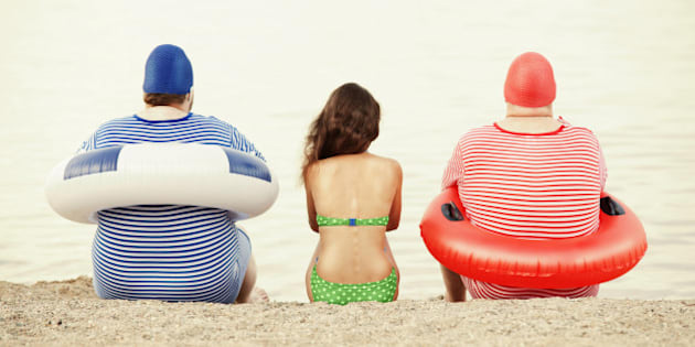 Two overweight men with slender woman sitting on beach
