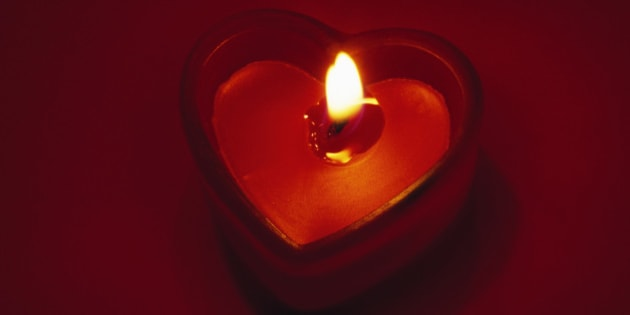Flame burning on heart-shaped candle, red background.