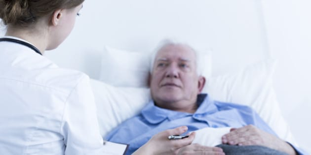 Doctor or nurse talking to elderly patient in hospital room