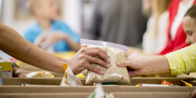 Young adults at a community service food bank, preparing boxes with food donations.