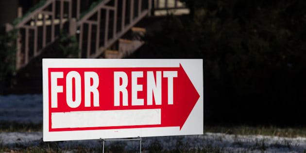 Image of a home for rent sign that has a red arrow.  Behind the sign is a blurry outline of wooden porch steps.  The real estate for rent sign has a blank space for contact information.  The yard has light snow on it.