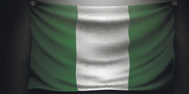 waving flag nigeria on a dark wall with a spotlight, illuminated