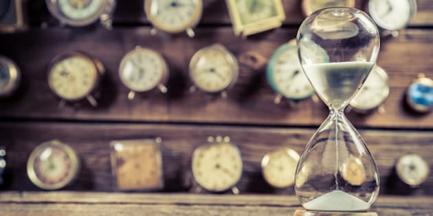 Old hourglass on the background of clocks.