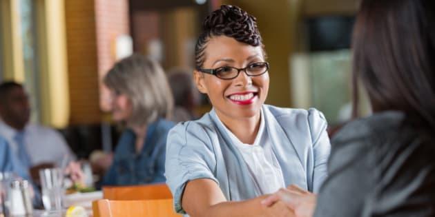 Modern businesswomen shaking hands during meeting or interview in restaurant