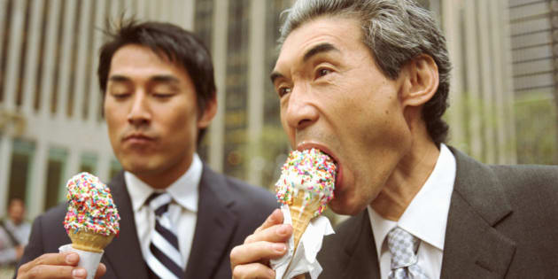 Two businessmen eating ice cream