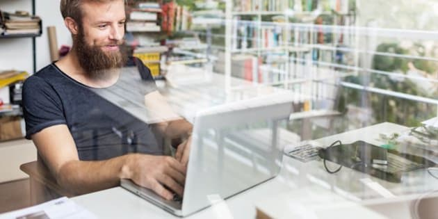 Young bearded man sitting on desk in his home office and working on laptop.