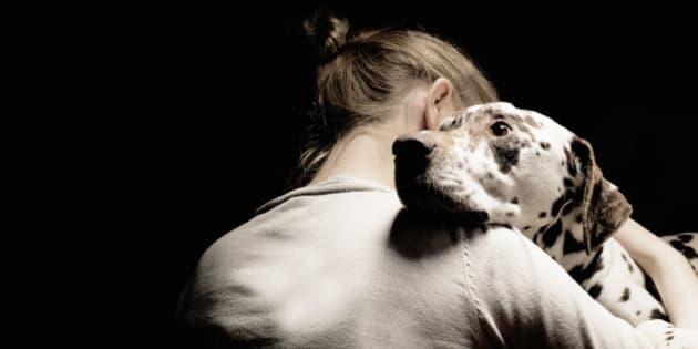 girl embracing her dog, studio shot