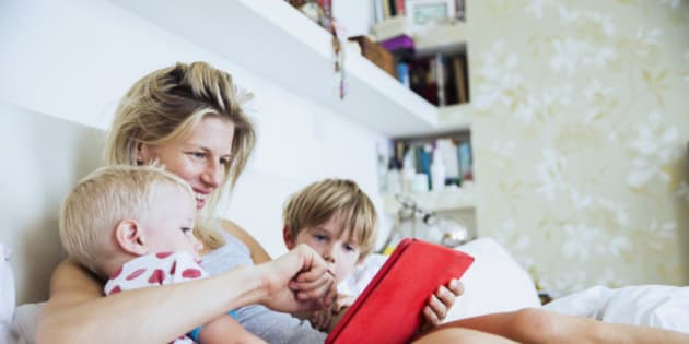 Mother with her sons watching tablet in bed