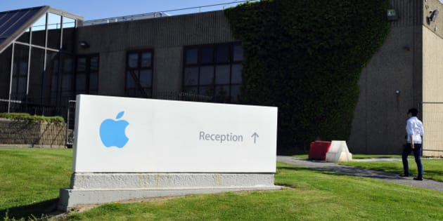 A pedestrian walks near a sign at Apple Inc.'s campus in Cork, Ireland, on Tuesday, June 4, 2013. Speaking to lawmakers in Dublin last month, Irish Finance Minister Michael Noonan insisted the country is no tax haven, after a congressional hearing in Washington focused attention on Apple Inc.'s maneuvers to minimize its tax bill through its operations in Cork in the south of Ireland. Photographer: Aidan Crawley/Bloomberg via Getty Images
