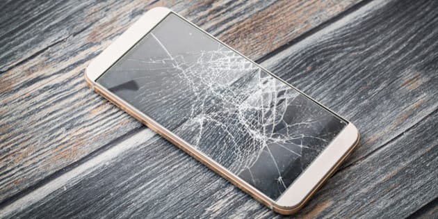 Modern broken mobile phone on wooden background.