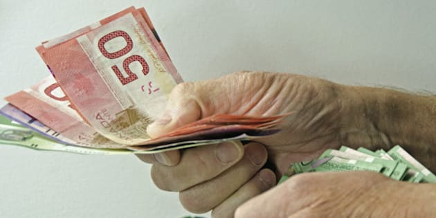 'A man's hands with a large amount of Canadian money handing it out to someone. Money for gifts,bills,mortgage'