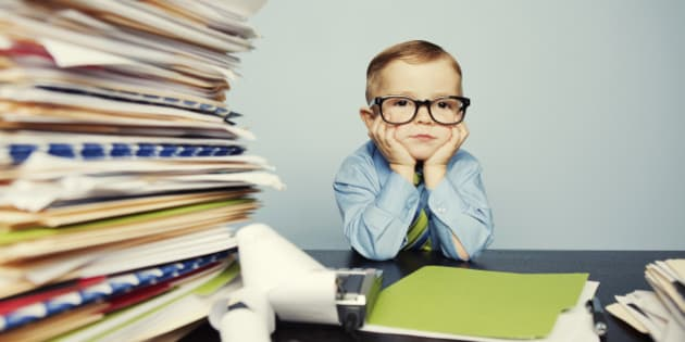 A young boy accountant has too much work to do at the office. Too much stress this tax season.